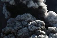 Malé letadlo vlevo nahoře prolétává kouřem a popelem vystupujícím ze sopky (Autor: Lucas Jackson)