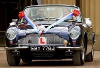 Novomanželé odjíždějí v kabrioletu Aston Martin DB6 Mark II