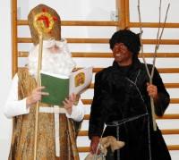 Mikuláš s čertem čtou z Knihy hříchů