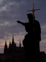Socha na Karlově mostě se siluetou Pražského hradu